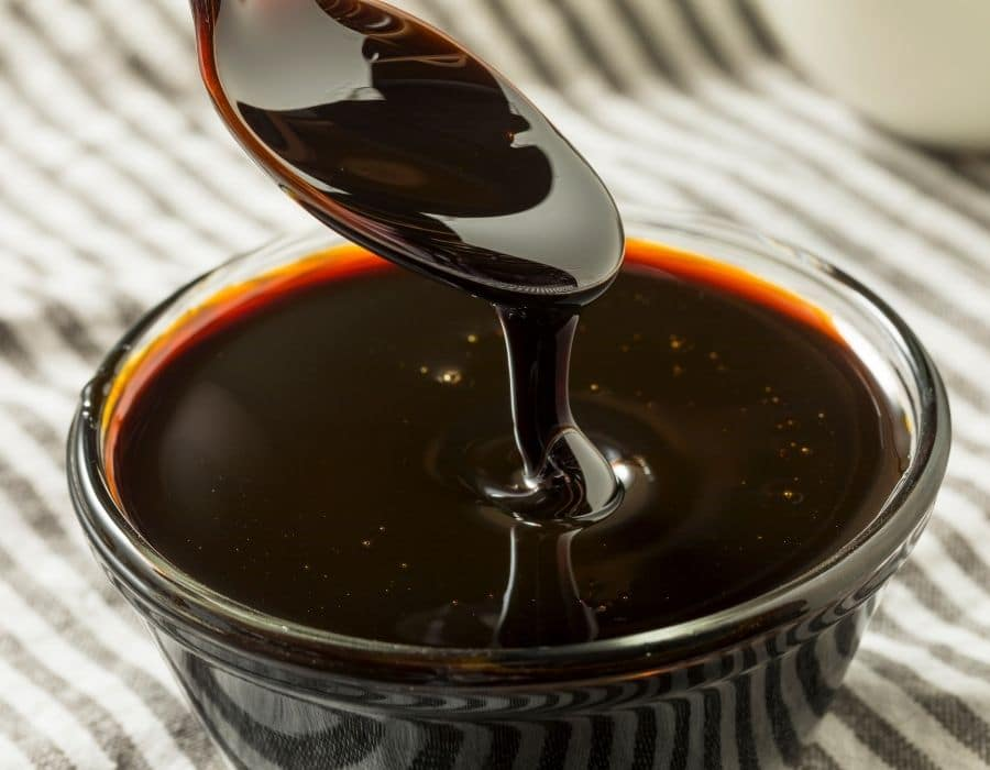 Spoon spooning molasses from glass jar to be used for cannabis nutrients